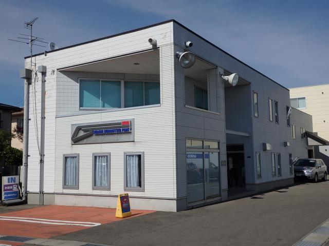 新車店舗・サービス工場裏に建屋がございます。建屋前オレンジ色のスペースが駐車場となっております。
